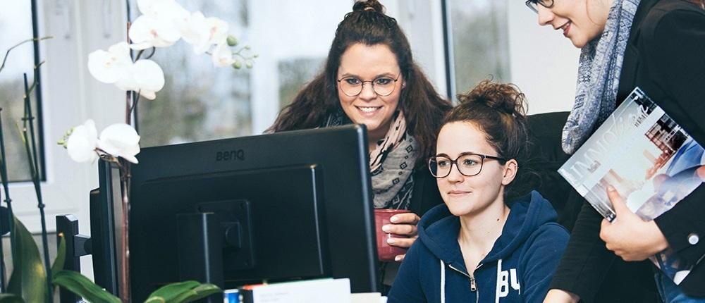 Drei Mitarbeiterinnen in der Diskussion am PC
