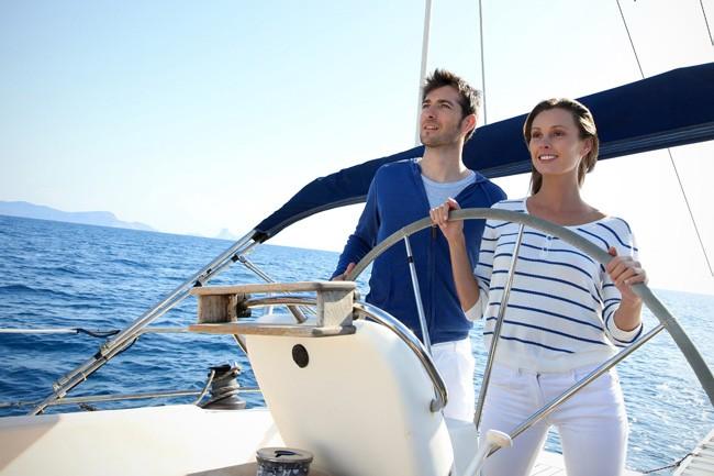 Eine Frau und ein Mann am Steuer eines Segelboots