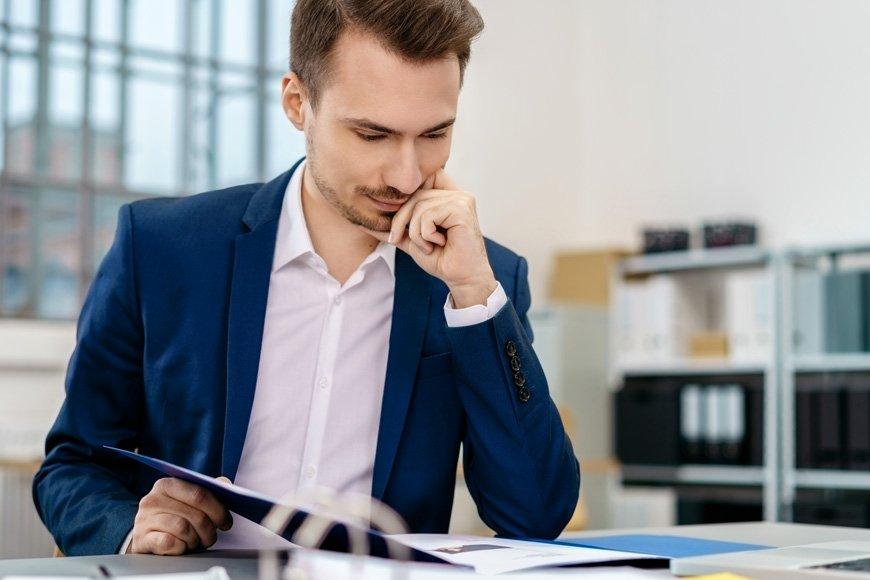 Junger Mann mit Anzug liest Presseinformtionen