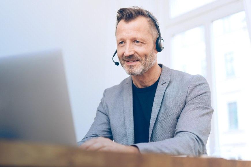 Ein Mann sitzt mit Headset am Laptop