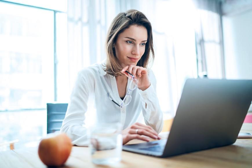 Eine Frau schaut sich ein Video am Laptop an