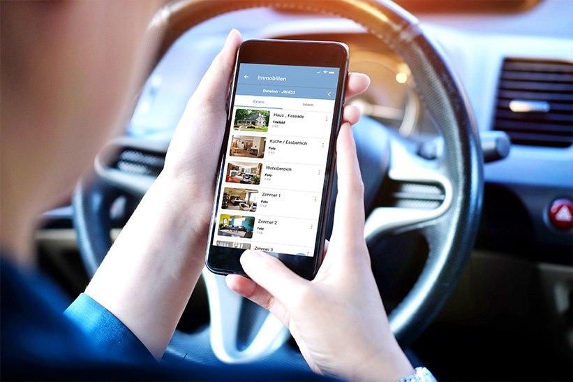 Eine Maklerin schaut sich die Immobilienfotos auf ihrem Smartphone an.