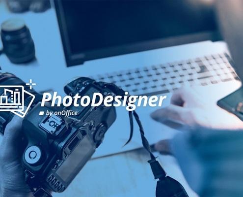 Ein Mann sitzt am Laptop und hält seine Kamera in der Hand